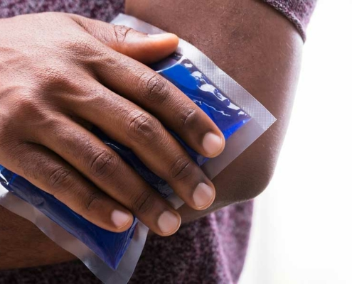 man holds an ice pack against the outside of his sore elbow